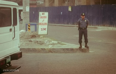 Unsure of what he's guarding, I steal a photo while speeding past this Manila officer from the anonymity of a taxi.