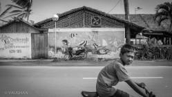 A boy on a bike passes me as I walk the streets alone.