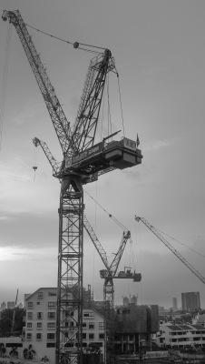 Nearby cranes over Singapore freeway.