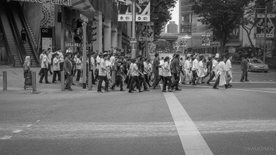 Pedestrians march as an army, minding the lights.