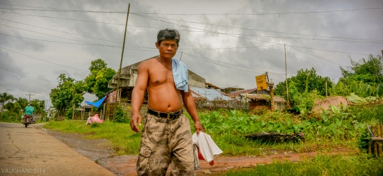 While on the back of a Tricycle motor bike, I caught this local farmer strolling along the road.