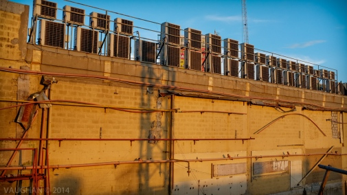 An apocalyptic array of rusted air-conditioning units atop abandoned building. Manila